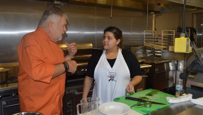 Culinary instructor and CAFÉ Partner Chef David Locke discusses the task at hand with CAFÉ senior Abby Figueroa.