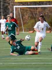 Yorktown's Segio Spinello (14) trips while being checked