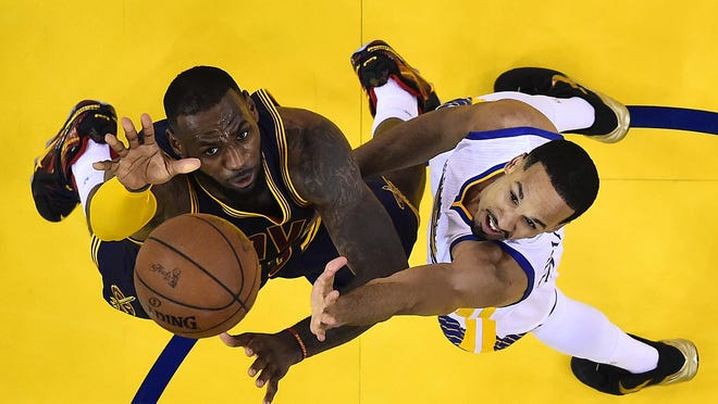 Cleveland Cavaliers forward LeBron James, left, reaches for the ball next to Golden State Warriors guard Shaun Livingston during the second half of Game 5 of basketball's NBA Finals in Oakland, Calif., Sunday, June 14, 2015. The Warriors won 104-91. (John G. Mabanglo/EPA Pool via AP)