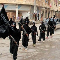 Image posted on a militant website shows fighters from the Islamic State marching in Raqqa, Syria, in 2014.