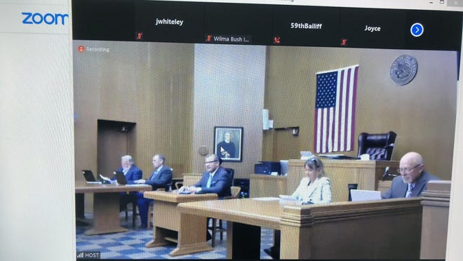 Grayson County commissioners meet in the east courtroom at the Grayson County Courthouse Tuesday. The meeting was shared through ZOOM to allow for social distancing.