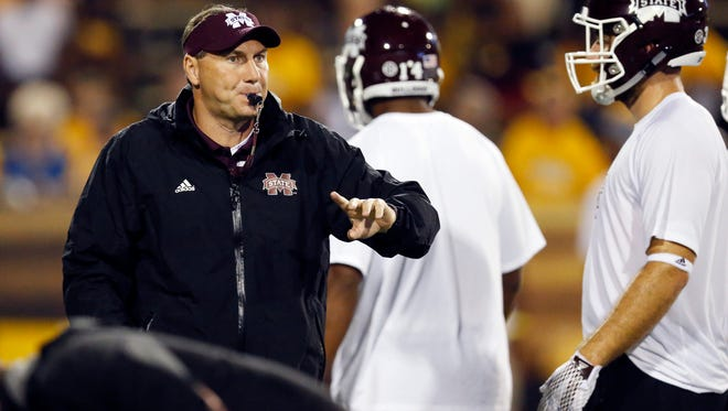 Mississippi State football coach Dan Mullen signals his team during warmups prior to an NCAA college football game against Southern Mississippi at M.M. Roberts Stadium in Hattiesburg Miss., Saturday, Sept. 5, 2015. Mississippi State won 34-16. (AP Photo/Rogelio V. Solis)
