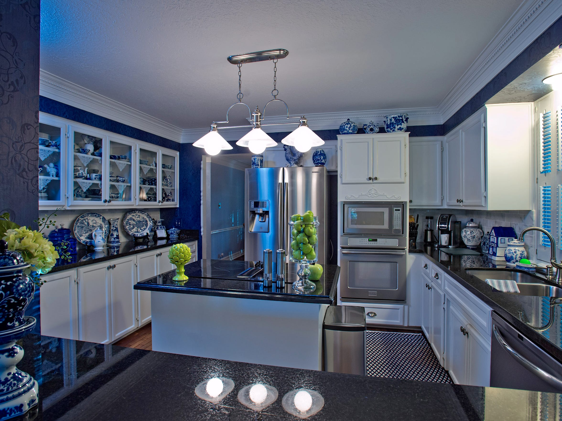 Black granite counters are perfect match for the stainless steel appliances and blue tones in the kitchen, featuring an island, breakfast bar  and plenty of built ins