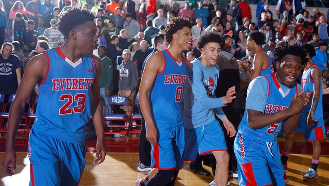 Everett players, including Victor Edwards (23), LeAndre Wright (0) and Markeese Reynolds (5), celebrate following their 54-48 regional final win over East Lansing Wednesday, March 16, 2016, at Mason High School.