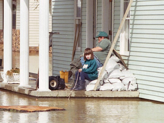 With flood water rising, David Chaney along with his daughters Katy, 12, (L) and Jessica, 6, watching after his dads house in Beals. MKL 3/7/97