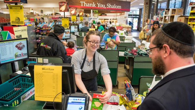 Cashier Megan Hook checks out groceries for Rabbi Michael Frank, 40, at a market in Silver Spring, Md.