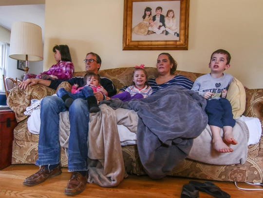From Left: Kate (7), Mave (2) Brian, Quinn (4) Liam (7) and Amy Harrington relax on the couch while watching Big East Basketball in their Wilmington home.