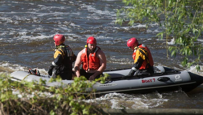 A man stranded in the middle of fast current on the Poudre River gets a ride in a boat from rescuers near College Avenue on Wednesday, May 16, 2018.