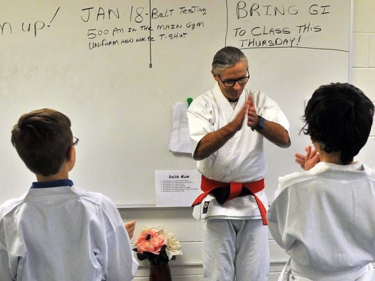 Kirby Middle School physical education and martial arts instructor Ray Silverstrand celebrates with one of his classes after a successful martial arts training session Jan. 12.