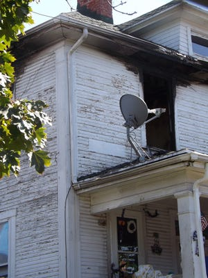 The damage from a Saturday night fire at 315 N. 21st St. is visible on the front and side of the home on Sunday afternoon.
