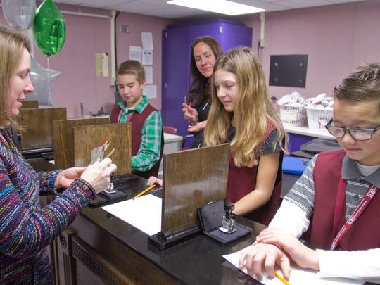 Mom Stephanie McKalko, left, makes a deposit in the LOC Federal Credit Union branch that just opened at Northwest Elementary School, run by students. Taking her deposit on Friday, Feb. 3, 2017 is her daugher, fifth grader Katherine McKalko, with, from left, William Meyer, LOC Youth & Community Development Coordinator Stephanie Cole and Micah Schrock on hand.