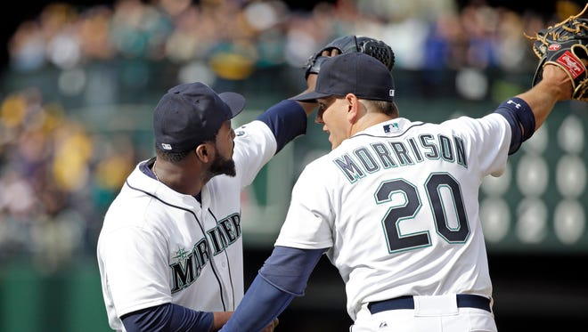 Seattle Mariners' Logan Morrison (20) joins closer Fernando Rodney in pointing toward the outfield after the team beat the Los Angeles Angels in a baseball game Monday, April 6, 2015, in Seattle. The Mariners won 4-1.