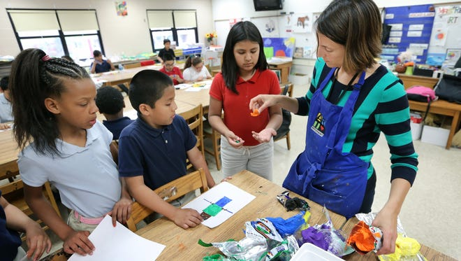 IPS School 96 art teacher Jamie Resh hands out clay for a project during an Art With a Heart after-school program.