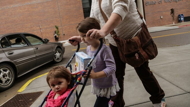 'It's awful. We don't use the water except for to flush the toilets. We buy gallons of water to fill up the bath tub to bathe the kids in because I'm scared they are going to get water in their mouth,' Tara Buckles of Flint said while walking out with her daughters Madison Buckles 5 of Flint and Anahlynn Buckles 2  with their free water filter while leaving the Michigan Department of Health Human Services in Flint on Tuesday October 6, 2015. Buckles who is currently pregnant goes to her mother's house outside of the city to shower and fill up well water to bring home. The state of Michigan provided the filters to residents with partnership from the Michigan Department of Health Human Services and the Genesee County Community Action Resource Department. The filters are part of Governor Snyder's water action plan for the city since high levels of lead have been found in the drinking water that comes from the Flint River.