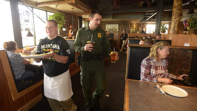 Mark Ardito of the U.S. Boarder Patrol serves drinks to Cheriene Downen at a McKenzie River Pizza during a previous Tip-A-Cop fundraiser for Special Olympics Montana.