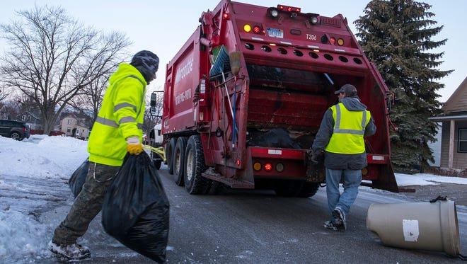 Marcotte Disposal employees Mickey Kenney, left, and Stephen Clark load garbage into the back of a garbage truck in a southside neighborhood Thursday morning. On Tuesday, Gov. Snyder signed an initiative that will increase garbage dumping fees.