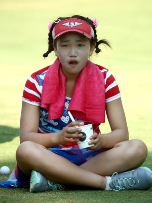 Eleven-year old amateur Lucy Li of the United States takes a break as she waits to hit on the third hole during the first round of the 69th U.S. Women's Open at Pinehurst Resort & Country Club, Course No. 2  on June 19, 2014 in Pinehurst, North Carolina.