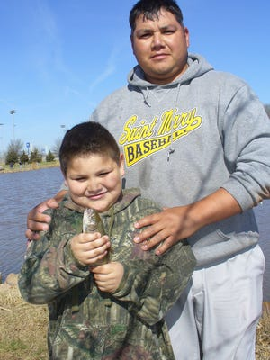 In this file photo, Cayson Salvador with his father, Jason Salvador, shows off  trout he caught at the Plum Lake Kid Fishing Rodeo. Rainbow trout will be stocked in dozens of ponds, lakes and rivers across Texas for fishing fun through the winter months. Trout stocking will begin Nov. 25 and continue through March 5.