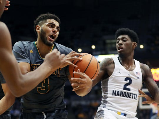 Vermont forward Anthony Lamb (3) fights with Marquette guard Sacar Anim (2) over a loose ball during a men's college basketball game in December.