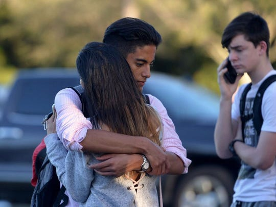 Jorge Zapata,16, a student at Marjory Stoneman Douglas High School in Parkland, Fla., embraces his mother, Lavinia Zapata, after a mass shooting on Feb. 14, 2018, at the school. Seventeen people died of injuries in the attack.