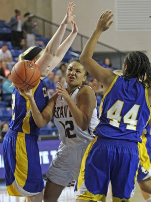 Caravel junior Micah Morgan powers under the defense of Sussex Central's Emily Truitt, left, and Jada Smack.