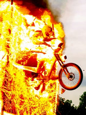 """John """"Mercury"""" Morgan rode his bicycle through a burning wall earlier this year during a festival hosted by Faith on Fire Fellowship."""