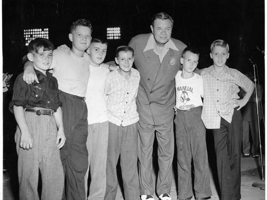 """Babe Ruth posed with a group of six lucky youngsters who got to come onto the field and meet the """"Sultan of Swat"""" in 1947."""