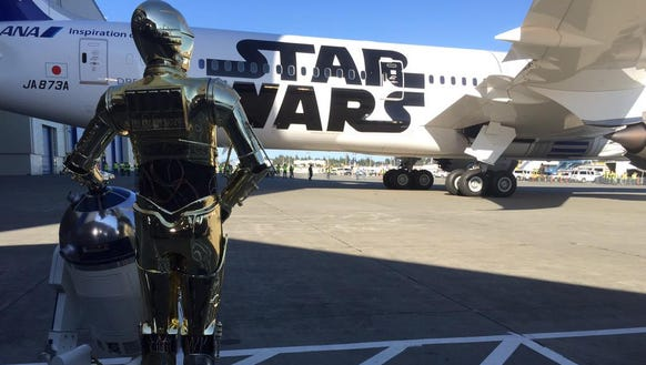 R2-D2 – joined by companion C3PO – watches as a Dreamliner