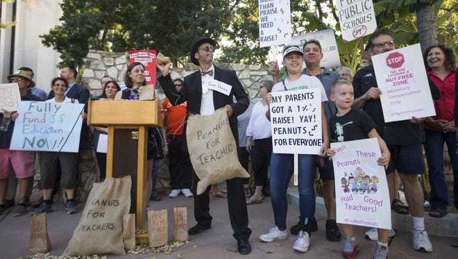 Dressed as Gov. Doug Ducey, Chris Fleischman throws peanuts to the crowd at a rally for teacher pay raises at the Arizona Capitol in Phoenix on Oct. 23, 2017.