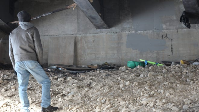 """Nick Toyne looks over a homeless camp under the 6th Street Bridge. """"One of the saddest things is when I find textbooks,"""" he said. """"That's when I know there was some kid there trying to stay in school."""""""