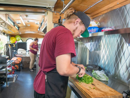 Collin Nelson, right, preps cilantro in the new Taco