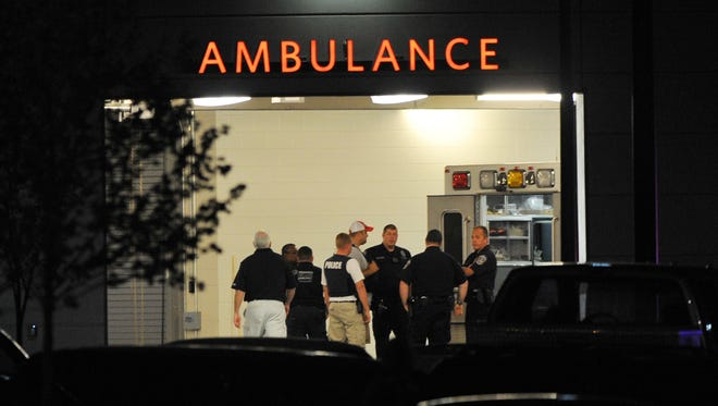 Law enforcement personnel gather in the ambulance bay at Eskenazi Hospital after a IMPD officer who was shot was transported there Saturday July 5, 2014.