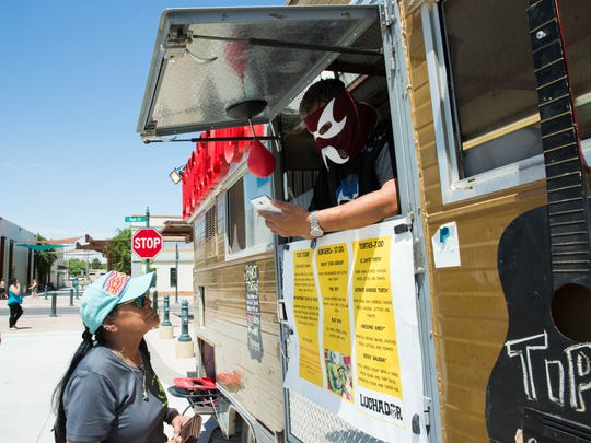 Ivan Saenz, right, owner and operator of the Luchador food truck, does business with customerFreda Firefly Flores during the Las Cruces Farmers and Crafts Market on Wednesday July 12, 2017.