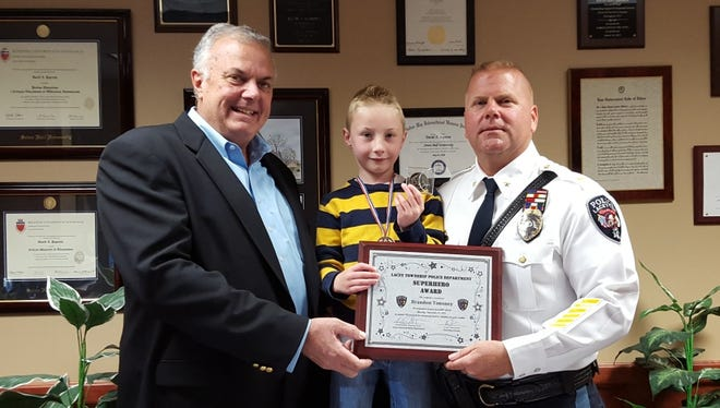 Lacey Mayor Gary Quinn and Police Chief David A. Paprota award Brandon Timoney a Superhero Award for helping to save his mother from a severe allergic reaction.