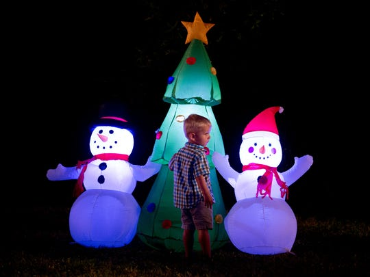 Blake Poe, 2, of West Palm Beach, views the displays at the Florida Oceanographic Coastal Center's inaugural Lights on the Lagoon, A Winter Wonderland, on Monday, Dec. 12, 2016, in Stuart. The nightly event opened Saturday and runs through Sunday, and features live entertainment, food and drinks.