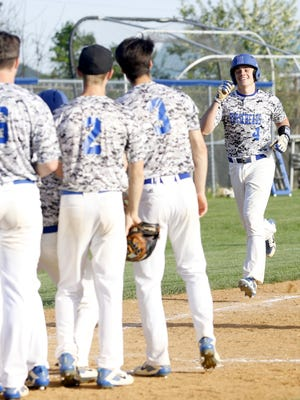 Horseheads players greet Andrew Thompson at home plate after his two-run homer May 21 in a 16-6 win over Corning in Game 1 of the Class AA championship series at Horseheads High School.