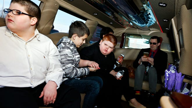 From left: Clay Marler, 12, Daniel Hawkins, 10, Brendan Marler, 11, and Danny Hawkins sit in a limousine that will take them to Brazilian restaurant ReRico in Springfield, Mo. on Feb. 9, 2017. The trip was a celebration by Williams' Elementary School's Brazil Club, which Hawkins leads, in recognition of the students' hard work learning about Brazil's language and culture.