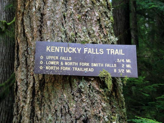 A sign provides distances to different points along the Kentucky Falls Trail.