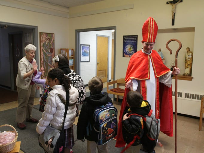 Principal Sister Kay Lurz and Father Morgan Rice CSB, dressed as St. Nicholas, greets students as they enter Saint Kateri School in Irondequoit for the day.