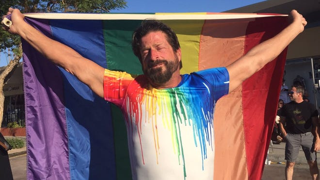 """""""It's a tragedy for America, and it's a tragedy for the gay community,"""" said Eric Adams, a Palm Springs resident who draped himself in a rainbow flag at the vigil in downtown Palm Springs Sunday, June 12, 2016."""