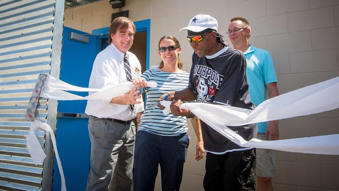 Las Cruces Mayor Pro Tem Greg Smith, left, Mesilla Valley Community of Hope Executive Director Nicole Martinez, Camp Hope resident Greg Ross and Matt Holt participate in a ribbon-cutting ceremony to open new bathroom and shower facilities at Camp Hope on Thursday, July 28, 2016.