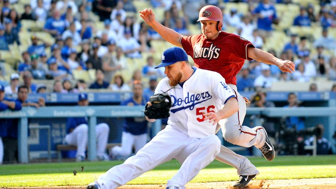 Los Angeles Dodgers relief pitcher J.P. Howell (56) covers home plate as Arizona Diamondbacks catcher Jordan Pacheco (31) runs in during the thirteenth inning at Dodger Stadium in Los Angeles on May 3, 2015. Pacheco would be called out on the play.