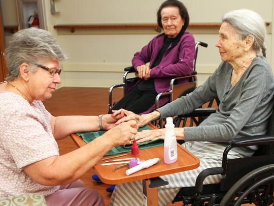 Freda Dawkins (middle), a resident at the Foothills Retirement Community nursing home in Easley, waits her turn for a manicure from Ireta Yarns (left) with Martha Caldwell (right). Yarns was a beautician for 47 years before living in the home.