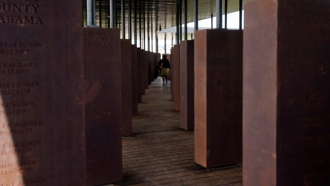 A visitor walks through memorials to lynching victims inside EJI's National Memorial for Peace and Justice in Montgomery, Ala., on Thursday, April 26, 2018.