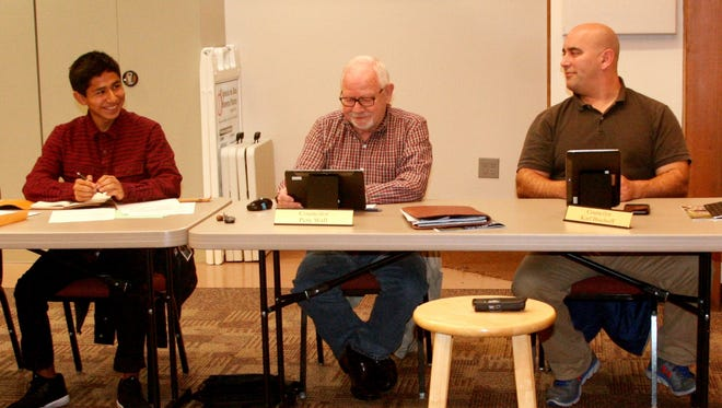 Noe Jinez discusses school business with Pete Wall and Karl Bischoff and the rest of the council on Dec. 5.