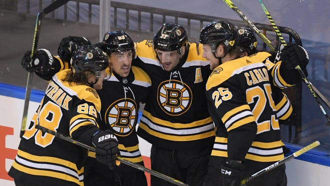 Bruins center Patrice Bergeron, second from right, celebrates with teammates after scoring the game-winning goal against the Carolina Hurricanes in the second overtime of Game 1 in the first round of the 2020 Stanley Cup Playoffs at Scotiabank Arena in Toronto.