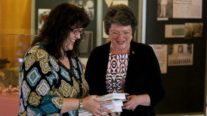 Jeanne Atkins, right, Oregon Secretary of State, looks at new copies of the Oregon Blue Book with Stacy Nalley, gift store coordinator, at the Capitol on Tuesday, March 17, 2015, in Salem, Ore.
