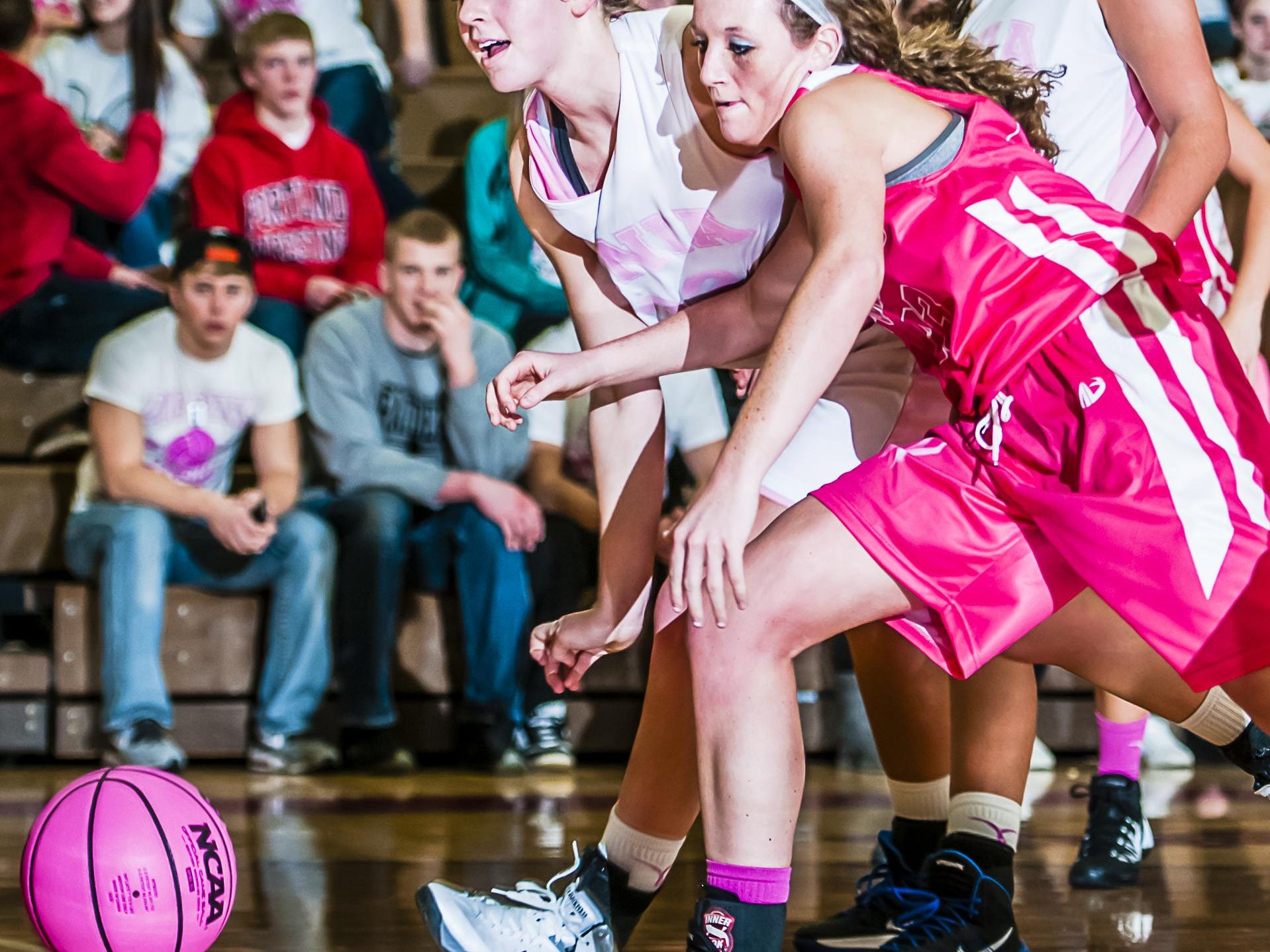 Sarah Swartz (left) of Ionia and Allie Grys of Portland go after a loose ball during a Coaches vs. Cancer game in 2014.