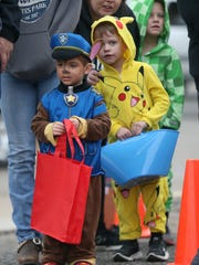 Trick-or-treaters wait in line for candy during the