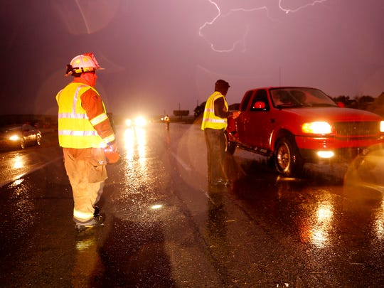 Valley Fire Department District 1 firefighters redirect traffic during an Aug. 26, 2015, storm on County Road 350 in the Crouch Mesa area.